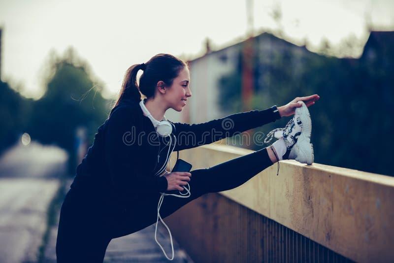 Den härliga flickan gör sträcka övning på bron arkivfoto