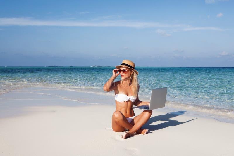 Den härliga flickan har en säsongsbetonad vintersemester på stranden i exotiskt land royaltyfria bilder