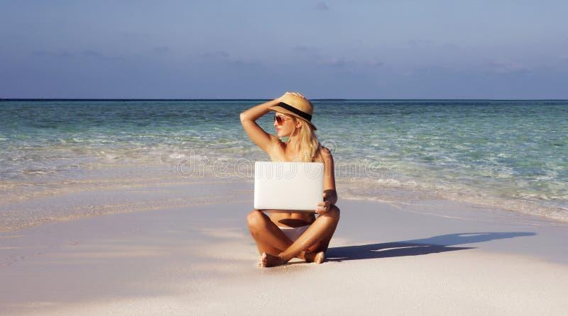Den härliga flickan har en säsongsbetonad vintersemester på stranden i exotiskt land fotografering för bildbyråer