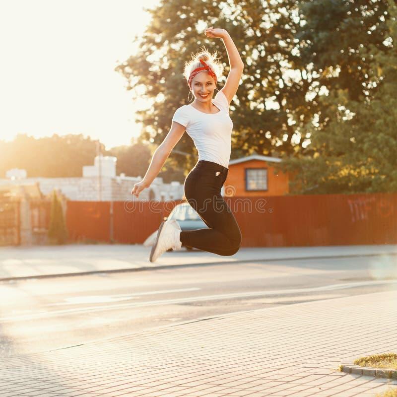 Den härliga flickan hoppade upp nära en väg på solnedgången arkivfoton