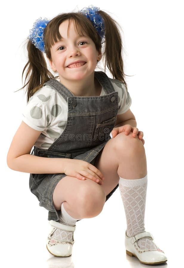 den härliga flickan hunker squats royaltyfri fotografi