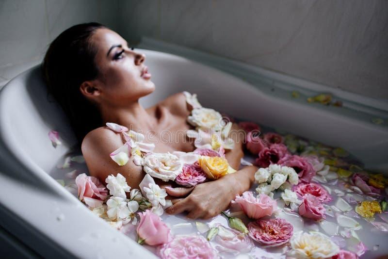 Den härliga flickan i badrummet med många blommar arkivfoton