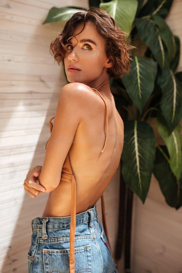 Den härliga flickan i beige bikini och grov bomullstvill kortsluter anseende med stora gröna sidor på bakgrund Stående av den ung royaltyfria bilder
