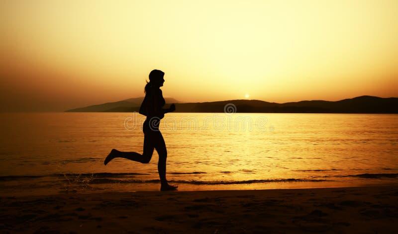 Den härliga flickan i bikini kör på stranden royaltyfria bilder