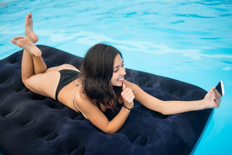 Den härliga flickan i bikini som ler och, gör selfiefotoet på telefonen på en madrass i pölen på semesterorten royaltyfria foton