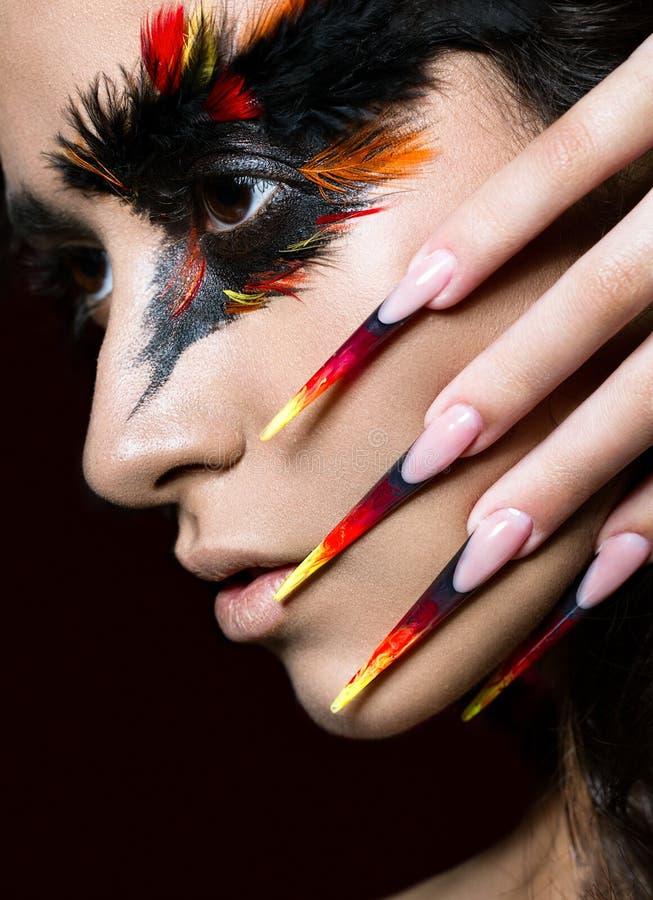 Den härliga flickan i bild av den Phoenix fågeln med idérik makeup och spikar länge Manikyrdesign Härlig le flicka arkivfoto
