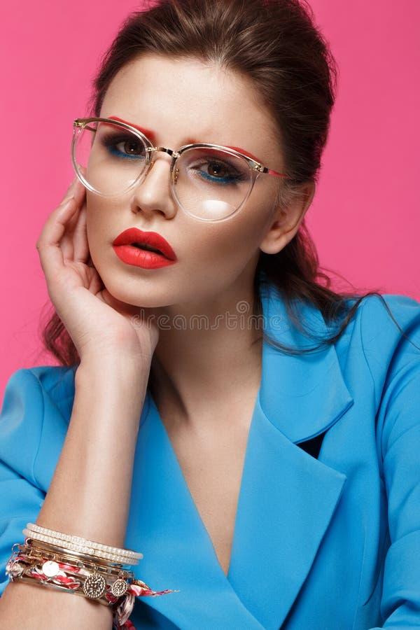 Den härliga flickan i blått passar på rosa bakgrund med idérikt smink och trendig stil Härlig le flicka royaltyfri foto