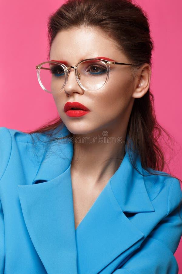 Den härliga flickan i blått passar på rosa bakgrund med idérikt smink och trendig stil Härlig le flicka royaltyfri fotografi
