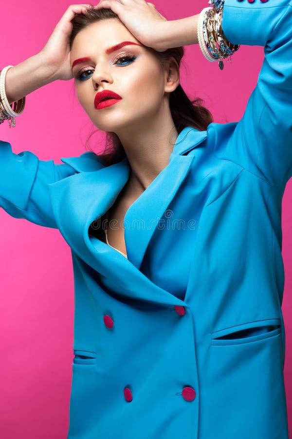 Den härliga flickan i blått passar på rosa bakgrund med idérikt smink och trendig stil Härlig le flicka royaltyfria foton