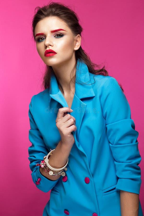 Den härliga flickan i blått passar på rosa bakgrund med idérikt smink och trendig stil Härlig le flicka royaltyfri bild