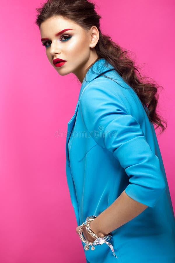 Den härliga flickan i blått passar på rosa bakgrund med idérikt smink och trendig stil Härlig le flicka arkivbilder