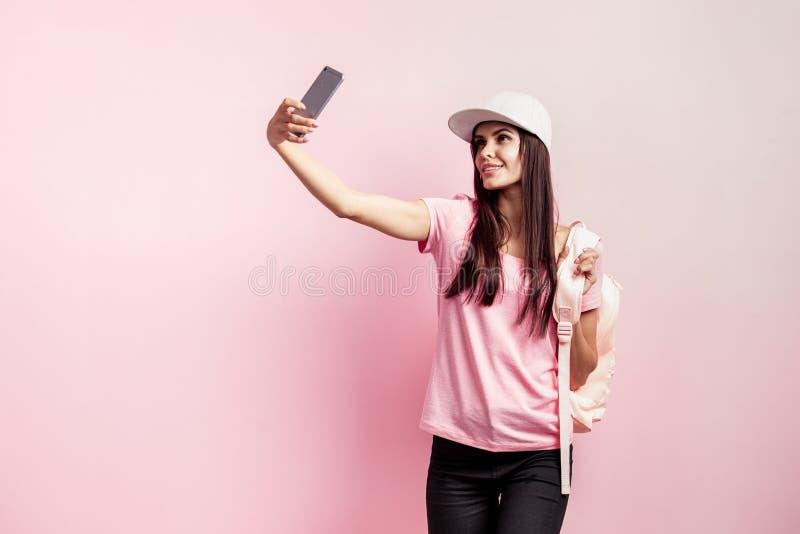 Den härliga flickan i det vita locket och med en ryggsäck på hennes svarta jeans för skuldror iklädda rosa t-skjorta och gör self arkivfoton