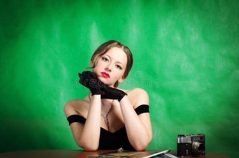 Den härliga flickan i en aftonklänning sitter på en tabell med tidskrifter och en rangefinderfilmkamera royaltyfri bild