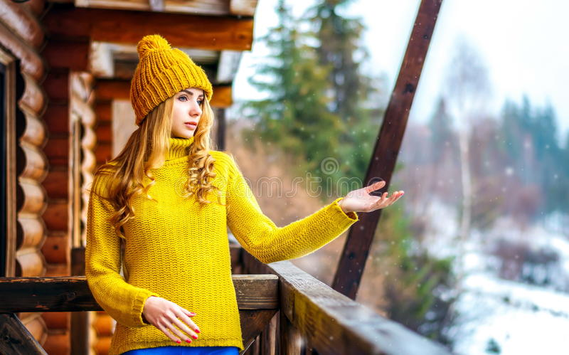 Den härliga flickan i en gul rät maskatröja och hatt fångar den snöhänderna och blicken royaltyfria foton
