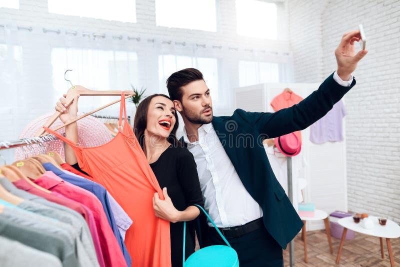 Den härliga flickan i en klänning och en attraktiv man i dräkt shoppar De är i en ljus visningslokal royaltyfri fotografi