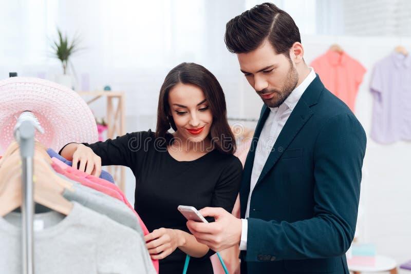 Den härliga flickan i en klänning och en attraktiv man i dräkt shoppar De är i en ljus visningslokal royaltyfri foto
