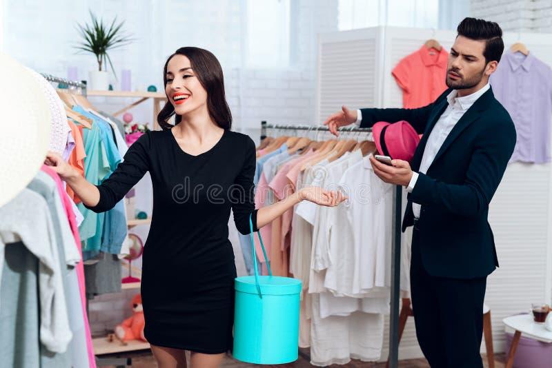 Den härliga flickan i en klänning och en attraktiv man i dräkt shoppar De är i en ljus visningslokal royaltyfria bilder