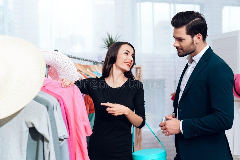 Den härliga flickan i en klänning och en attraktiv man i dräkt shoppar De är i en ljus visningslokal arkivfoto