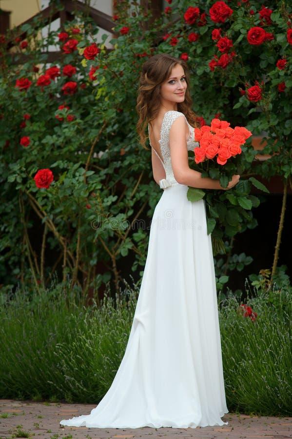 den härliga flickan i en lång vit klänning med buketten blommar royaltyfria bilder