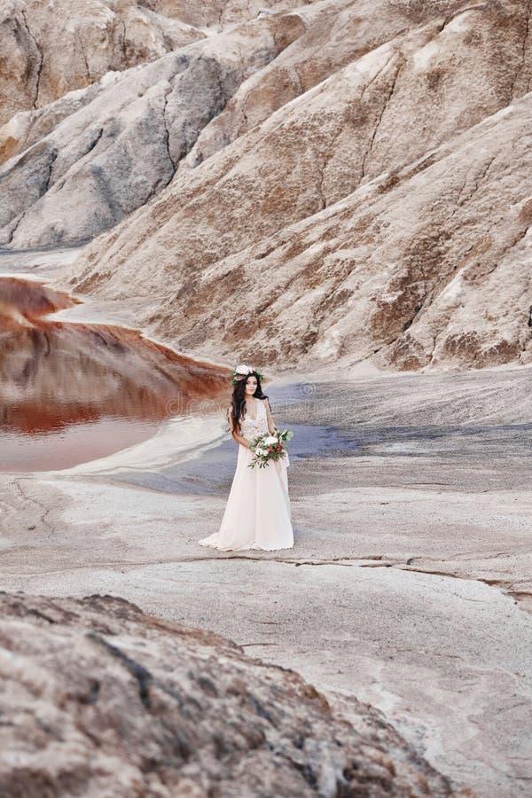 Den härliga flickan i en ljus sommarklänningbeiga går i mountaen royaltyfria foton