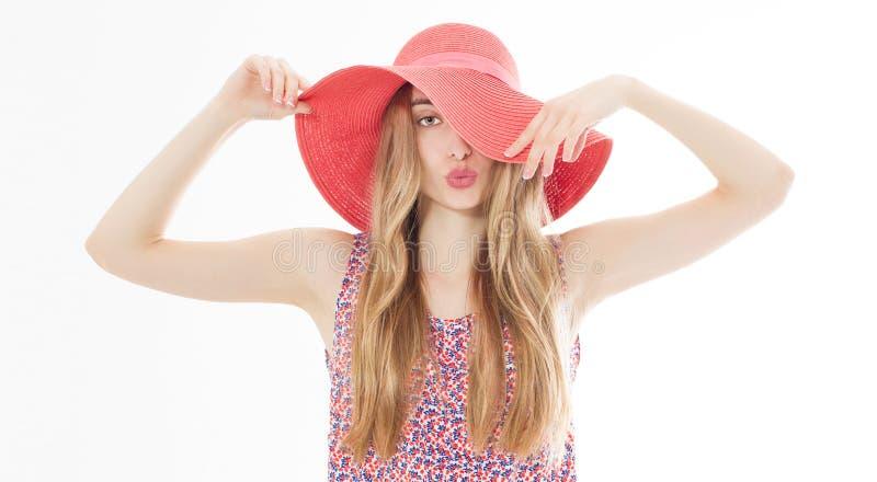 Den härliga flickan i en röd hatt som ler på sommarbakgrunden, isolerade royaltyfri fotografi