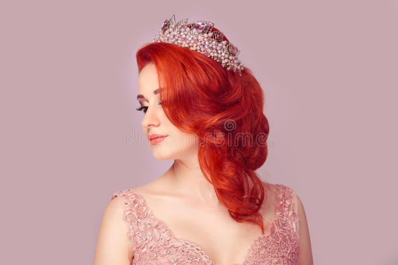 Den härliga flickan i en rosaaktig färg pryder med pärlor kronan som ser till frisyren för sidovisningen royaltyfri fotografi