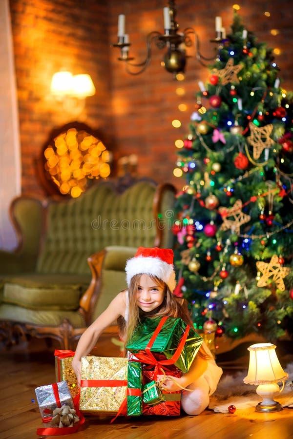 Den härliga flickan i en Santa Claus hatt sitter på golvet nära julgranen arkivbilder
