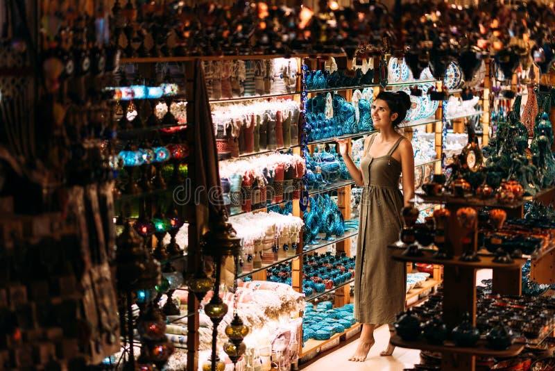 Den härliga flickan i en souvenir shoppar i Turkiet Flickan väljer en souvenirösterlänning shoppar Gatan shoppar turkiska souveni royaltyfri bild