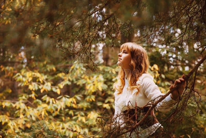 Den härliga flickan i en tappningklänning som går i en sommartid, parkerar Träd Skog arkivbild