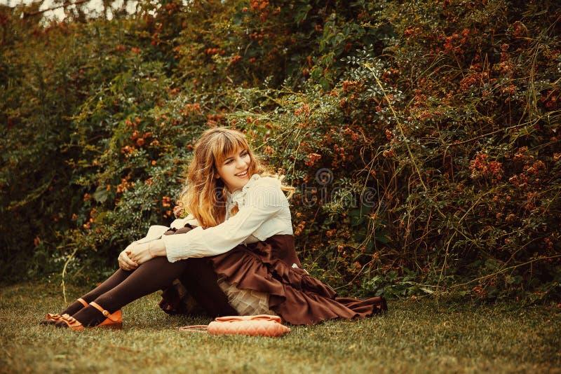 Den härliga flickan i en tappningklänning i en sommartid parkerar ro royaltyfria bilder