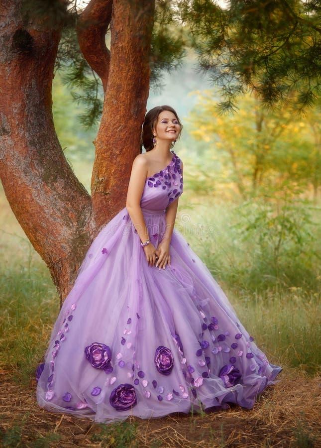 Den härliga flickan i en ursnygg lila klär anseende under ett träd royaltyfri bild