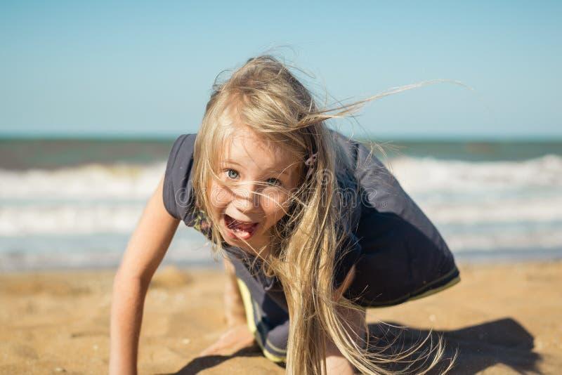 Den härliga flickan i grå färgklänning gör en gladlynt framsida på sanden av havet fotografering för bildbyråer
