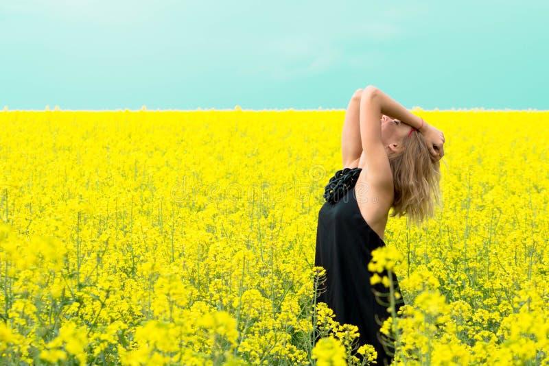 Den härliga flickan i guling blommar mot den blåa himlen royaltyfri foto