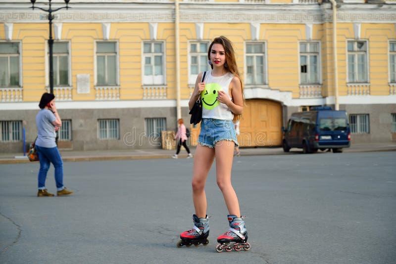 Den härliga flickan i kortslutningar rider på rullskridskor på slottfyrkant royaltyfria bilder