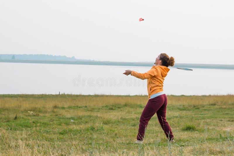 Den härliga flickan i ljus sportswear spelar badminton på kust av sjön royaltyfri bild
