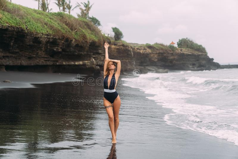 Den härliga flickan i mörk baddräkt går på den svarta sandstranden nära havet royaltyfri foto