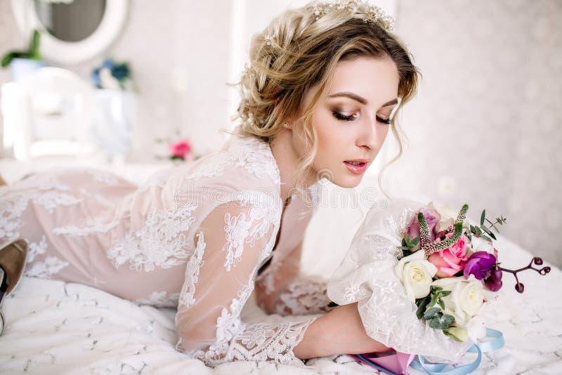 Den härliga flickan i mjuk spets- klänning med buketten blommar pioner i händer som står mot blom- bakgrund i blomsterhandel Joyf fotografering för bildbyråer