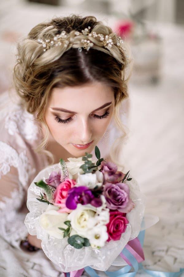 Den härliga flickan i mjuk spets- klänning med buketten blommar pioner i händer som står mot blom- bakgrund i blomsterhandel Joyf arkivbilder