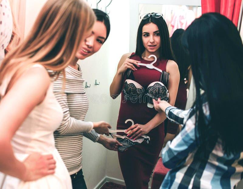 Den härliga flickan i röd klänning försöker på henne behån Hon ser hennes vänner, medan de ser behån och royaltyfria bilder