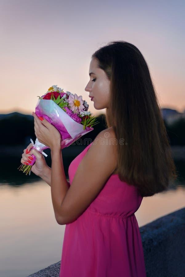 Den härliga flickan i rosa klänning rymmer en bukett av blommor royaltyfria bilder