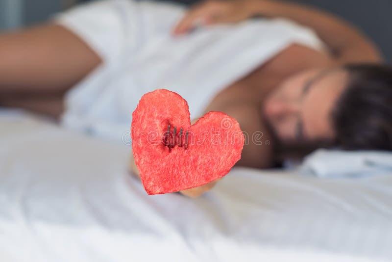 Den härliga flickan i säng ger hjärta från vattenmelon på en gaffel fotografering för bildbyråer