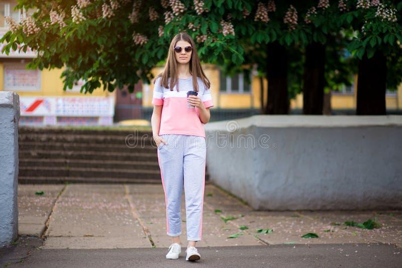 Den h?rliga flickan i solglas?gon g?r vid sommargatan med kaffe fotografering för bildbyråer