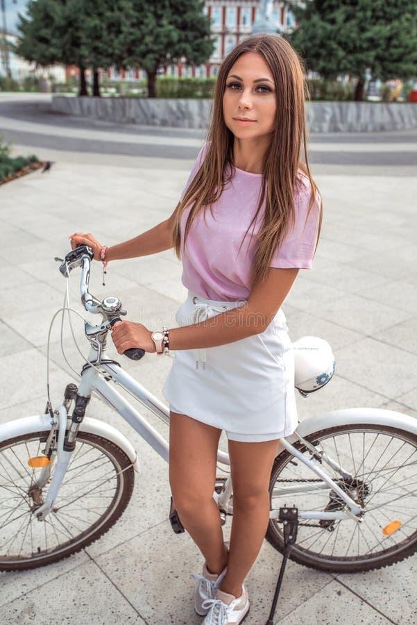 Den härliga flickan i sommaren i stad, står på med en cykel, helg vilar, den aktiva livsstilen, den rosa T-tröja, den vita kjolen royaltyfria foton
