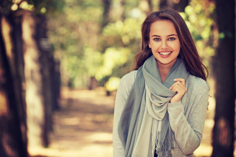 Den härliga flickan i stilfull modekläder i höst parkerar royaltyfri fotografi