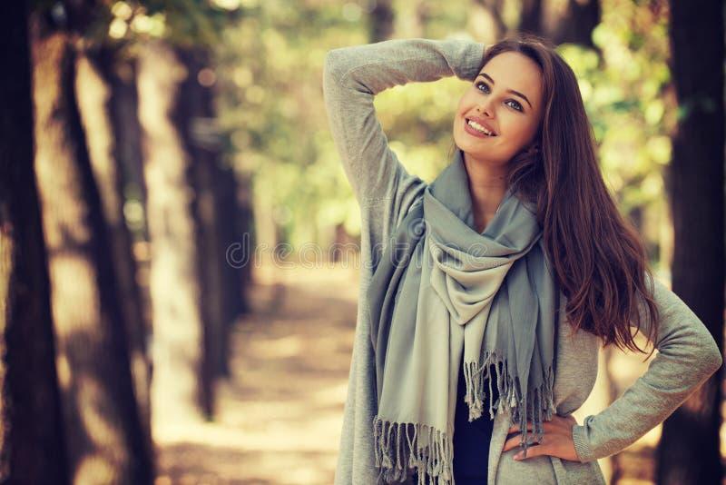Den härliga flickan i stilfull modekläder i höst parkerar royaltyfria bilder