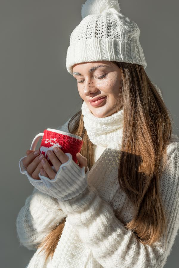 den härliga flickan i stilfull vintertröja och halsdukinnehavkopp te isolerade arkivbilder