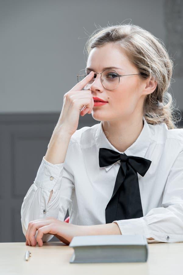 Den härliga flickan i stilfulla exponeringsglas sitter royaltyfria bilder