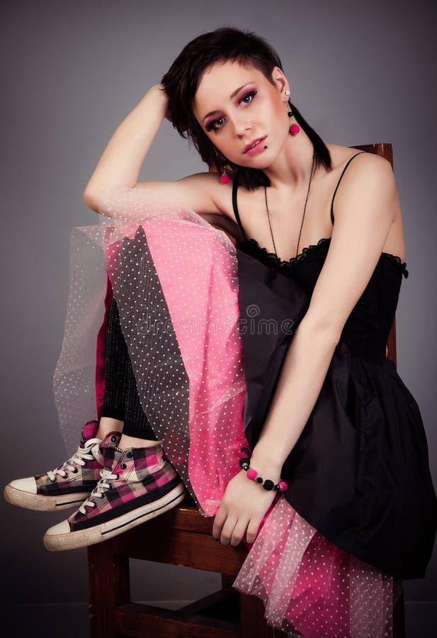Den härliga flickan i svart och rosa färger klär och gymnastikskor som sitter på enlagd benen på ryggen stol arkivfoton