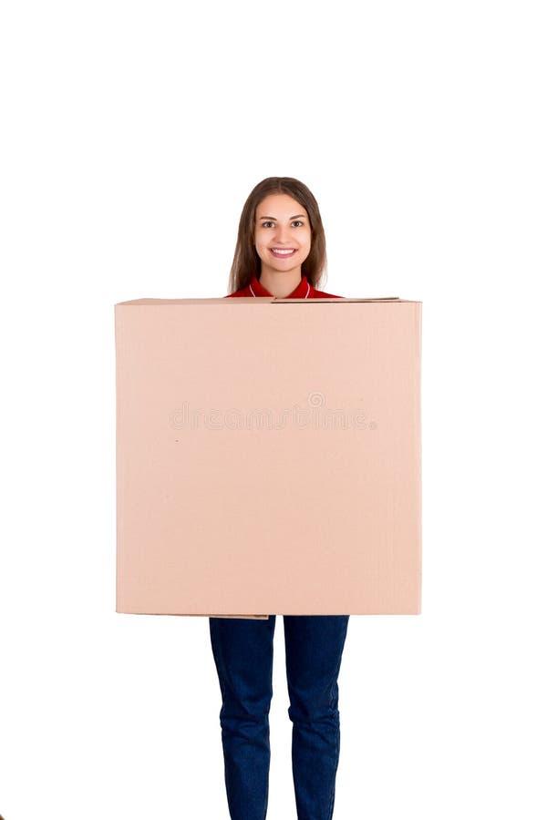 Den härliga flickan levererar en enorm jordlott till en kund När du ler kvinnan i arbetskläder rymmer en ask isolerad på vit royaltyfria bilder