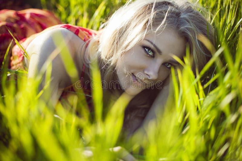 Den härliga flickan ligger i ett grönt gräs arkivfoto